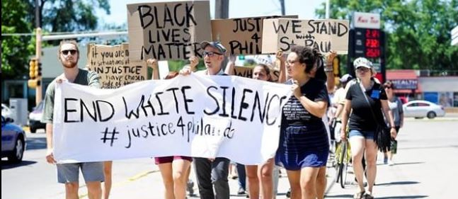 Picture of marchers holding End White Silence banner